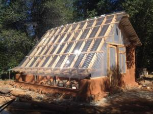 Earthen greenhouse - roundwood frame w/ cob & strawbale