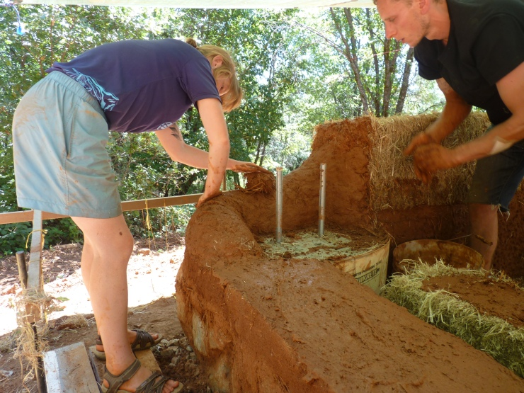 starting to add the Straw bales and slip, as we cob the corners.